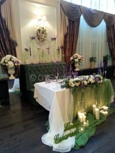Украшение стола жениха и невесты цветочной композицией и свечами