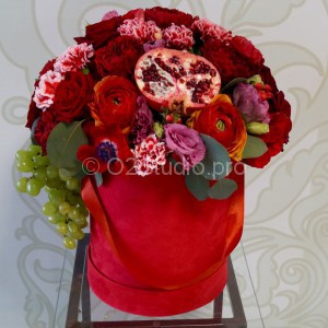 Цветы и фрукты в шляпной коробке в яркой бордово-красной цветовой гамме. Состав: ранункулюсы, анемоны, английские розы, гранаты Стоимость: 9200р