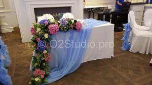 Украшение стола молодоженов ниспадающей тканью и цветочной композицией