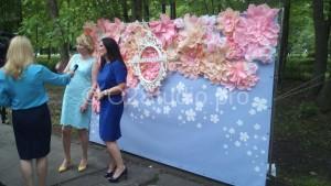 Родственники молодоженов дают интервью на фоне цветочного пресс волла